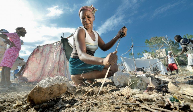 A woman digs with a machete as she builds a temporary home in a spontaneous camp for quake survivors being established in Croix-des-Bouguets, Haiti, north of the capital Port-au-Prince. Quake survivors continue to move as aftershocks continue, and reports of aid deliveries in one camp will provoke families from other camps to migrate there.
