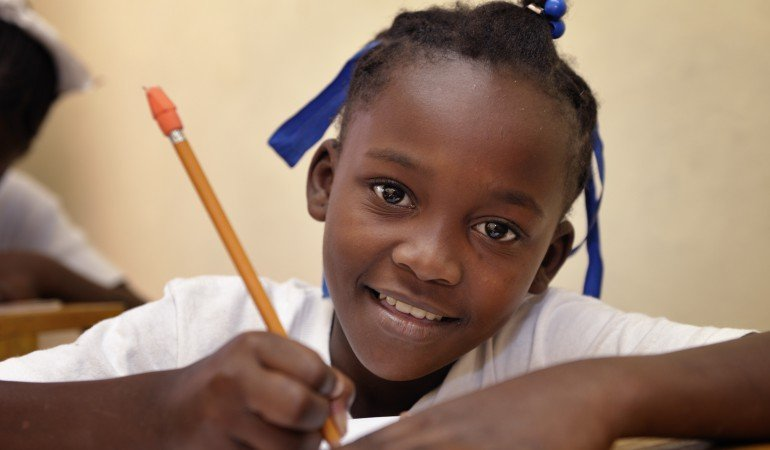 "A girl in class at the ""House of Hope,"" a community-based educational training program in Port-au-Prince, Haiti, for children performing domestic work (so-called 'restaveks'), sponsored by the Ecumenical Foundation for Peace and Justice (FOPJ).  Participants in the program also include former gang members and teenage mothers. Many rights activists consider the use of restaveks to be a modern form of slavery. They are usually children from extremely poor families who are sent away to work as domestic servants in wealthier homes. The children aren't paid for their work, but provided shelter and a sometimes meager meal supply. In the best case scenarios, families will send their restavek children to school. But restaveks often work long days performing a variety of household tasks for nothing more that a meal or two a day. Two-thirds of restaveks are girls, and they are extremely vulnerable to rape and sexual abuse from the families who house and control them. The life of a restavek child in Haiti often varies between bleak and hopeless, and many children never successfully leave their slave conditions. The ""House of Hope,"" which is supported by Church World Service, a member of the ACT Alliance, has begun to change that cycle of oppression for some restavek children  (Fondation Oecumenique Pour la Paix et la Justice.)"