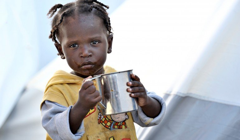 A young survivor of Haiti's devastating January 12 earthquake drinks water outside her family's tent in a displaced person's camp in the Belair section of Port-au-Prince. Wter, tents and other support for the camp have been provided by the ACT Alliance.